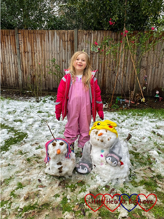 Sophie with her two snowmen in the back garden
