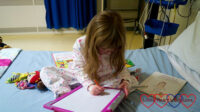 Jessica on her bed in the cardiac ward drawing a picture