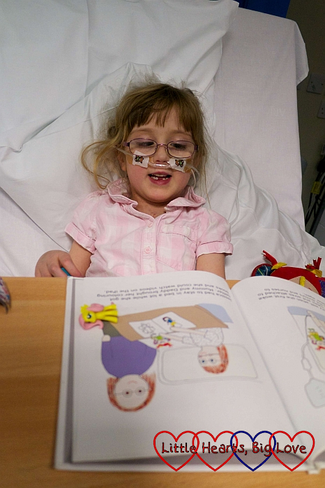 Jessica in high dependency looking at her book which I wrote to help prepare her for her surgery