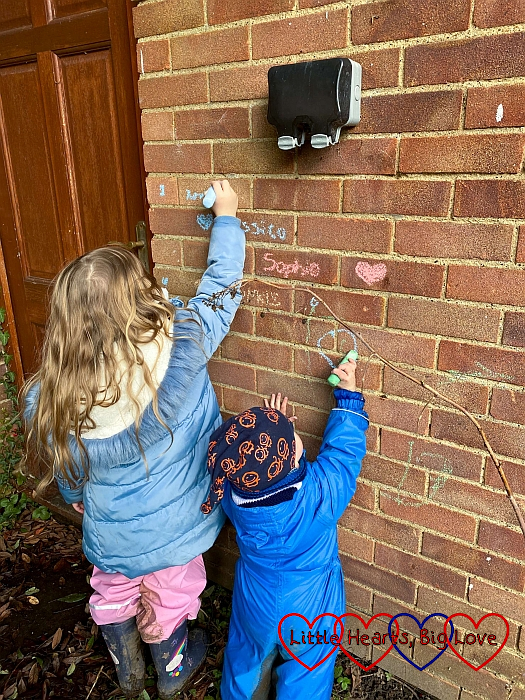 Sophie and Thomas drawing on a wall with coloured chalk