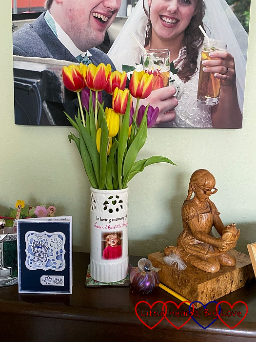 A vase of rainbow coloured tulips next to the wooden carving of Jessica