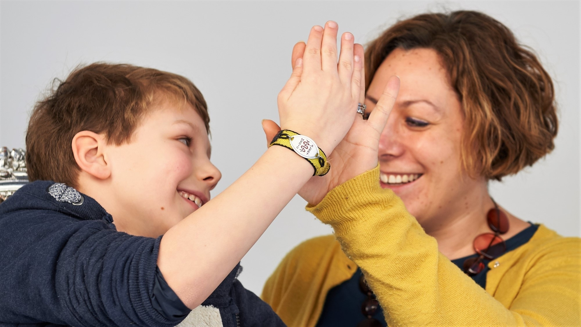 A boy wearing a MedicAlert bracelet gives a woman a high-five