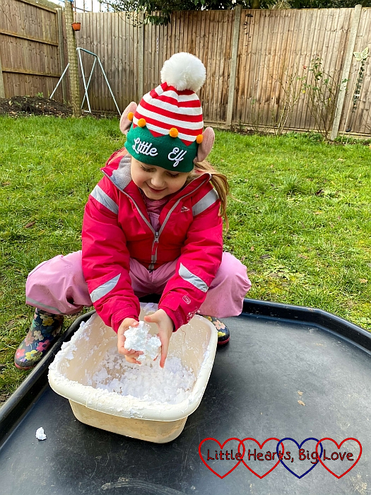 Sophie making a snowball with fake snow