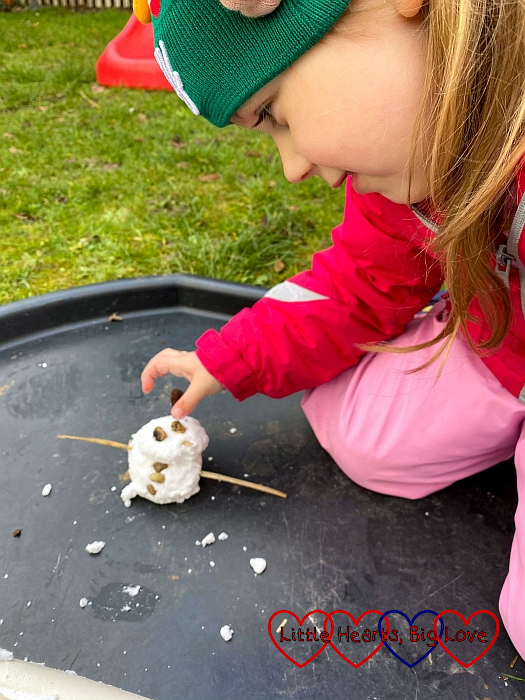 Sophie making a snowman with fake snow