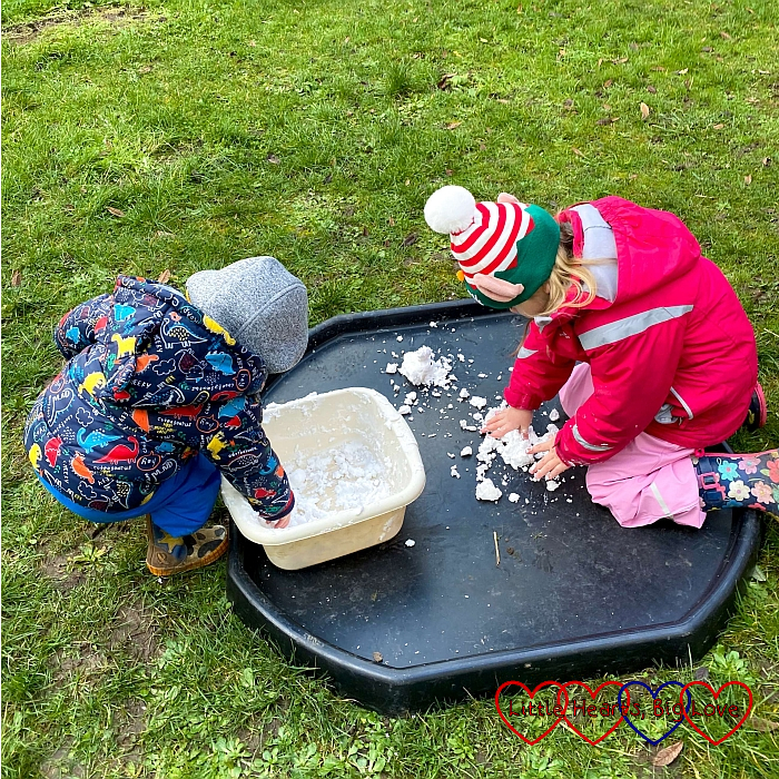 Sophie and Thomas playing with fake snow in the tuff tray in the garden