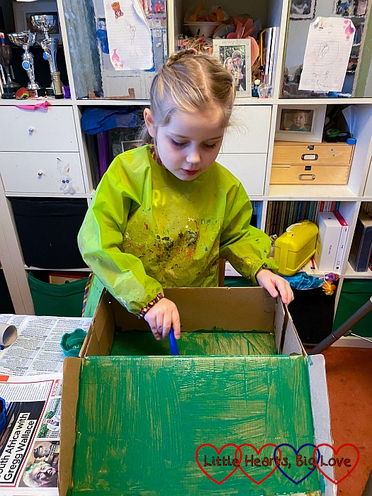 Sophie painting the inside of a shoebox with green paint