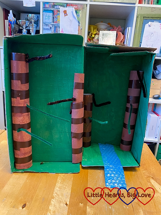 A green-painted shoebox with brown toilet roll tube tree trunks with pipe cleaners inserted for branches and a blue-painted bubble wrap river