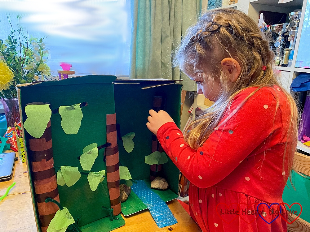 Sophie glueing tissue paper leaves on to the pipe cleaner branches of her trees in her shoebox rainforest