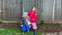 Sophie and Thomas in the garden with Sophie holding a picture of Jessica