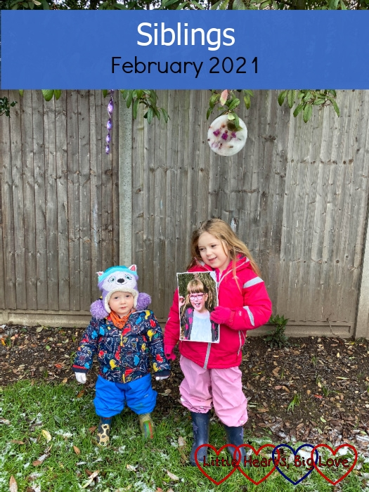 "Sophie and Thomas in the garden with Sophie holding a picture of Jessica - ""Siblings - February 2021"""