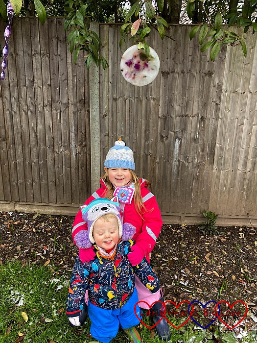 Sophie and Thomas with their ice suncatcher hanging in the tree above them