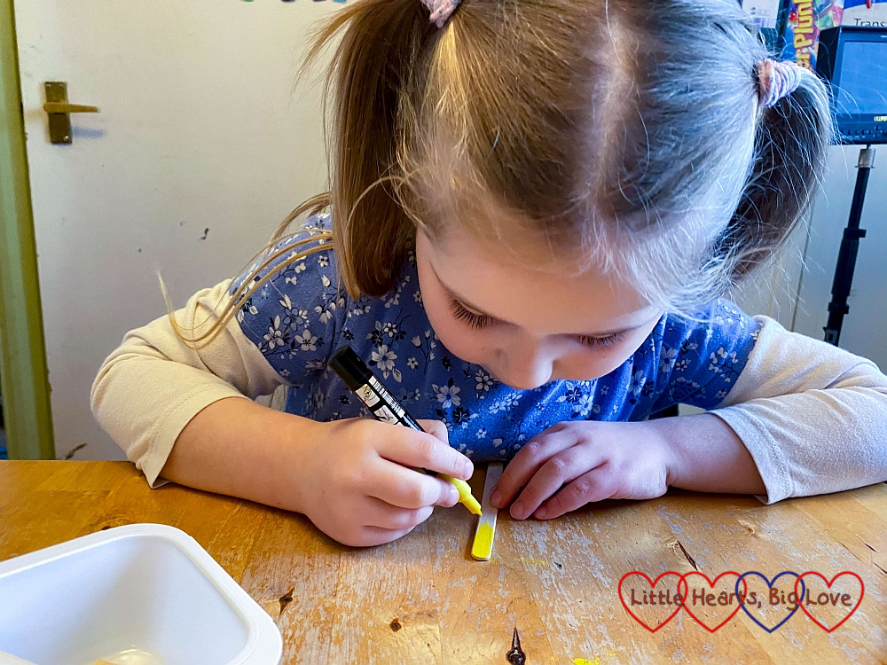 Sophie painting a craft stick with a yellow paint pen