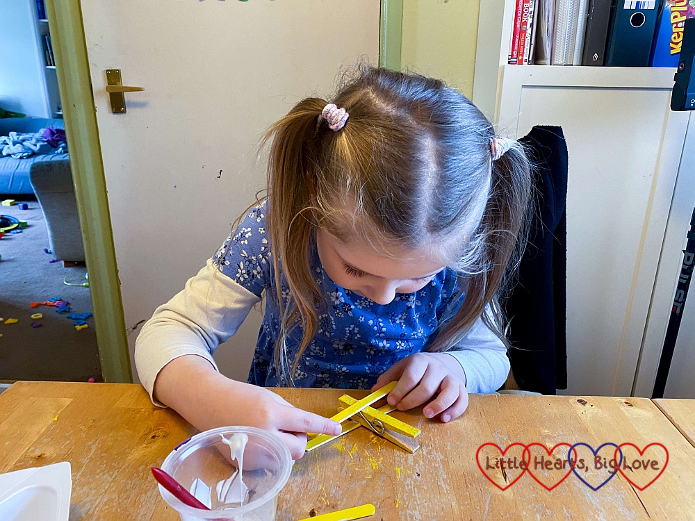 Sophie glueing the long pieces of craft stick to the front of the clothes peg