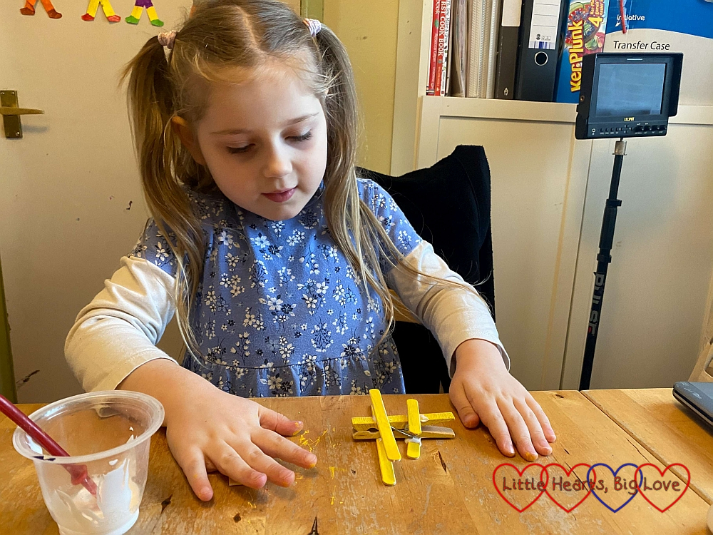 Sophie glueing the half-sized pieces of craft stick to the back of her clothes peg