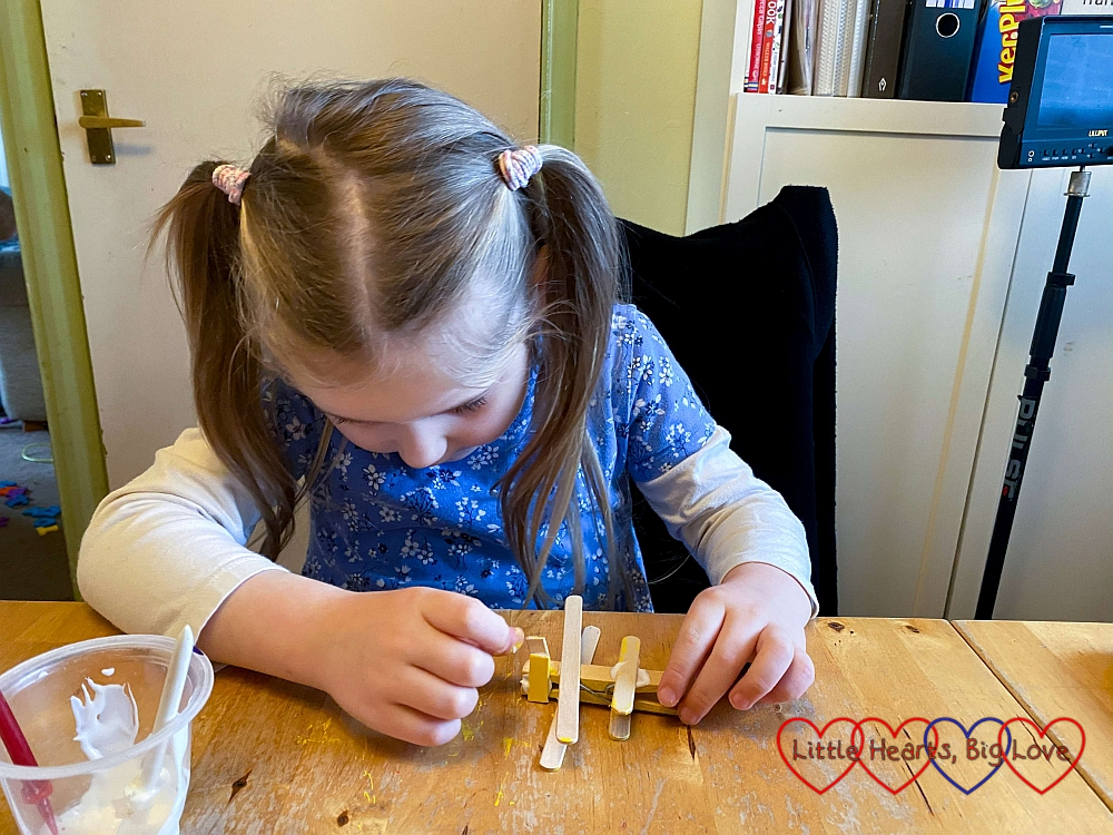 Sophie glueing the short pieces of craft stick to the front of the clothes peg