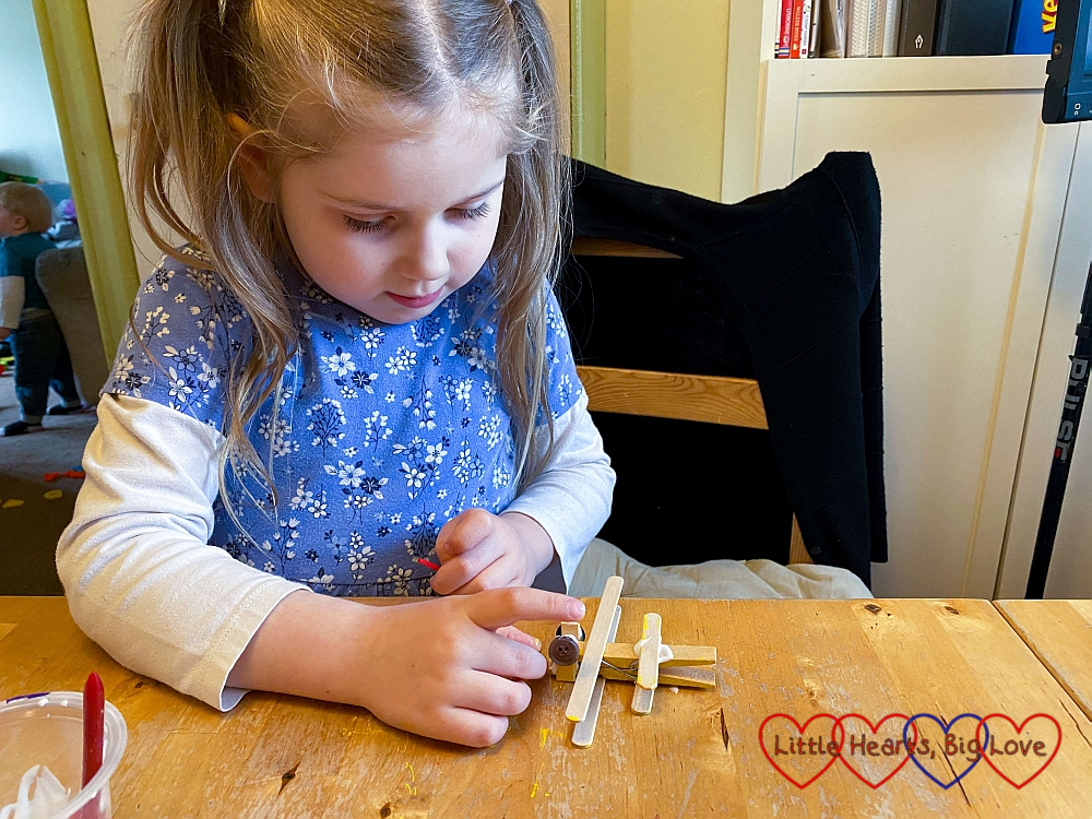 Sophie glueing buttons to the short pieces of craft stick