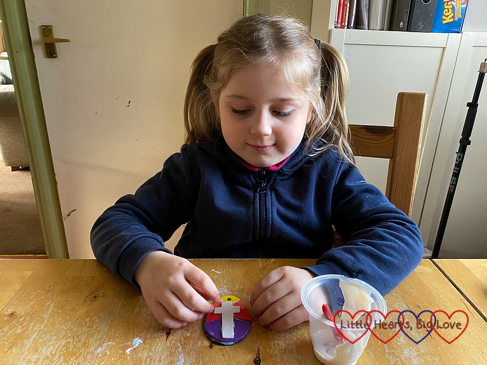 Sophie glueing a white cross to her craft foam egg shape