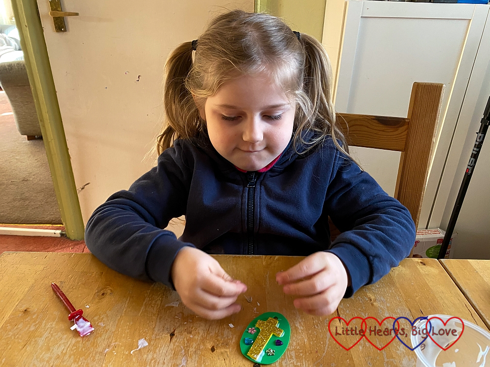 Sophie gluing jewels to her craft foam egg shape