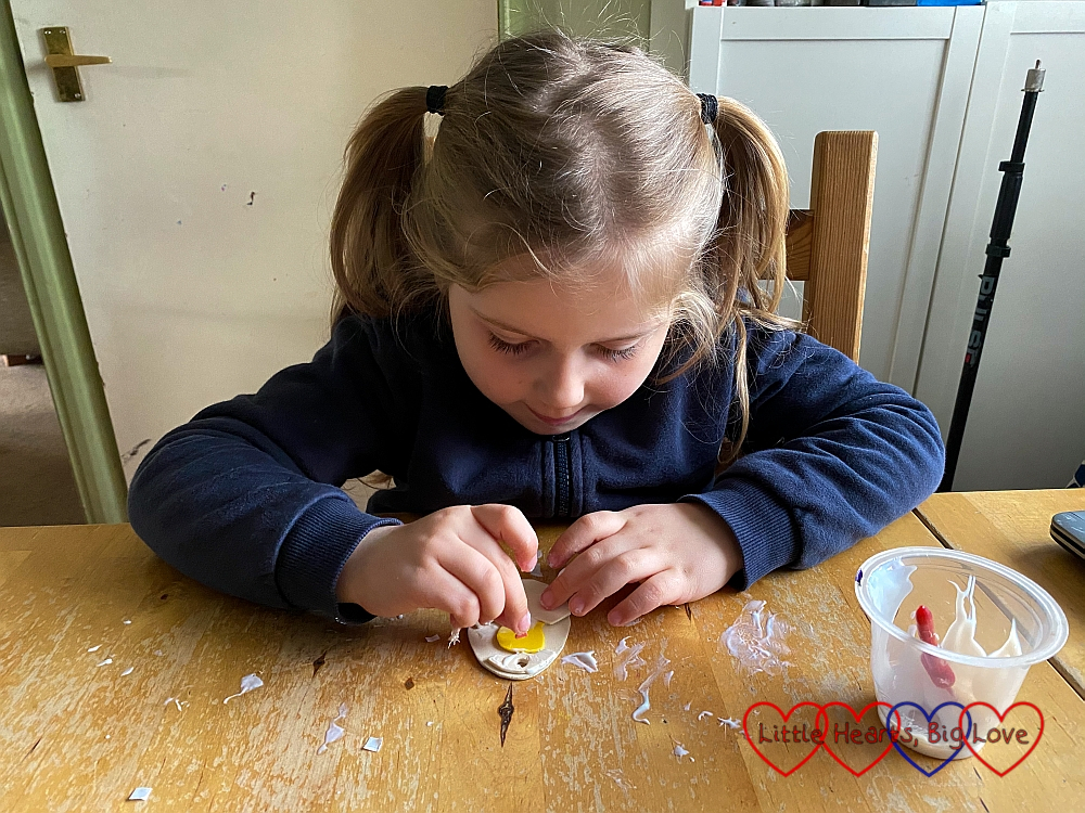 Sophie gluing the beak to her craft foam chick