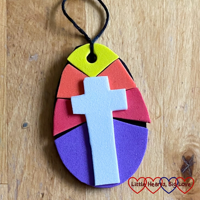 A craft foam Easter egg decoration showing a white cross against a coloured background