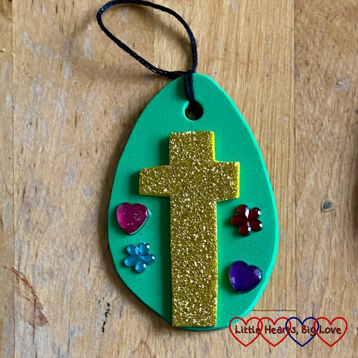 A craft foam Easter egg decoration showing a glittery white cross on a green egg shape surrounded by small craft jewels