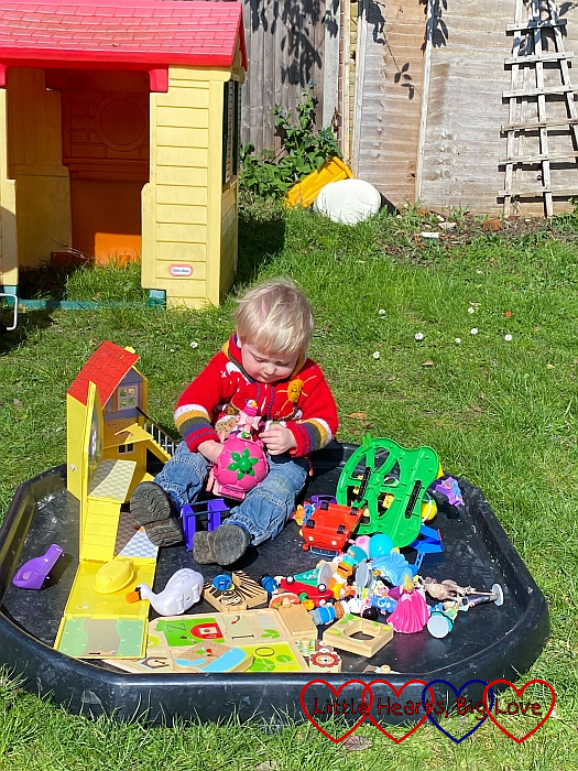 Thomas sitting in the tuff tray in the garden playing with toys