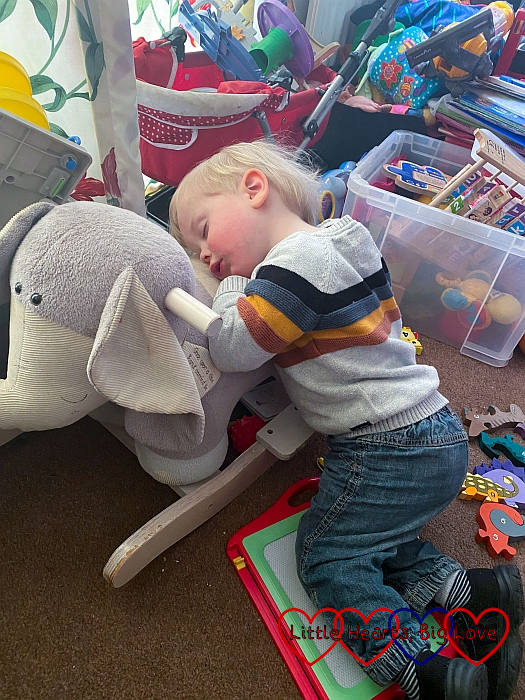 Thomas asleep on his knees leaning against his rocking elephant