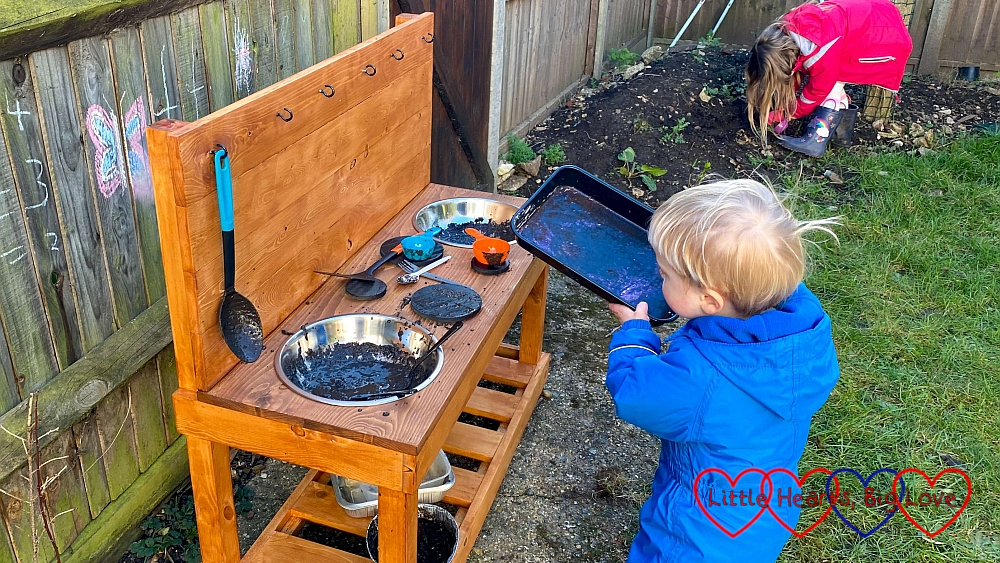 Thomas standing by the mud kitchen holding a tray