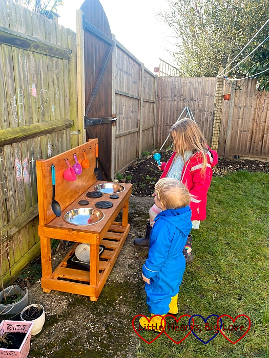 Sophie and Thomas looking at their new mud kitchen
