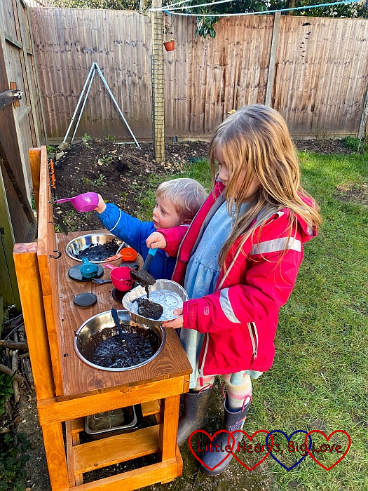 Thomas taking utensils off the hooks on the mud kitchen while Sophie spoons mud into a foil tray