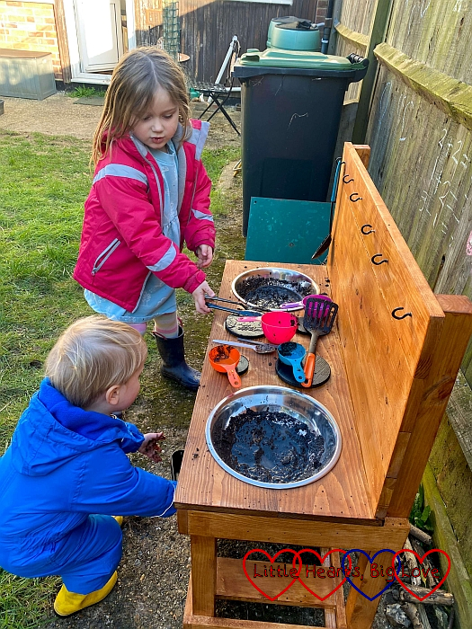 Sophie and Thomas playing with their mud kitchen