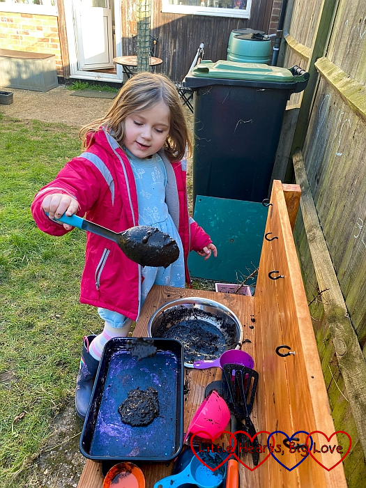 Sophie at the mud kitchen spooning mud into a baking tray
