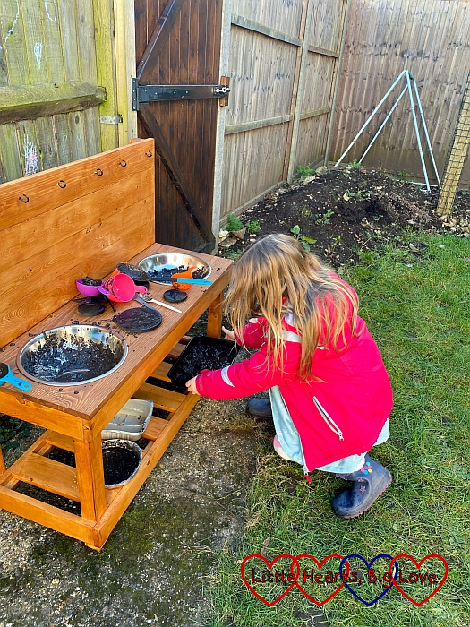 Sophie putting a baking tray full of mud on the bottom shelf of the mud kitchen