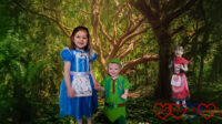 Sophie (dressed as Alice in Wonderland), Thomas (dressed as Peter Pan) with a forest background with Jessica (dressed as Little Red Riding Hood) peeping out from behind a tree