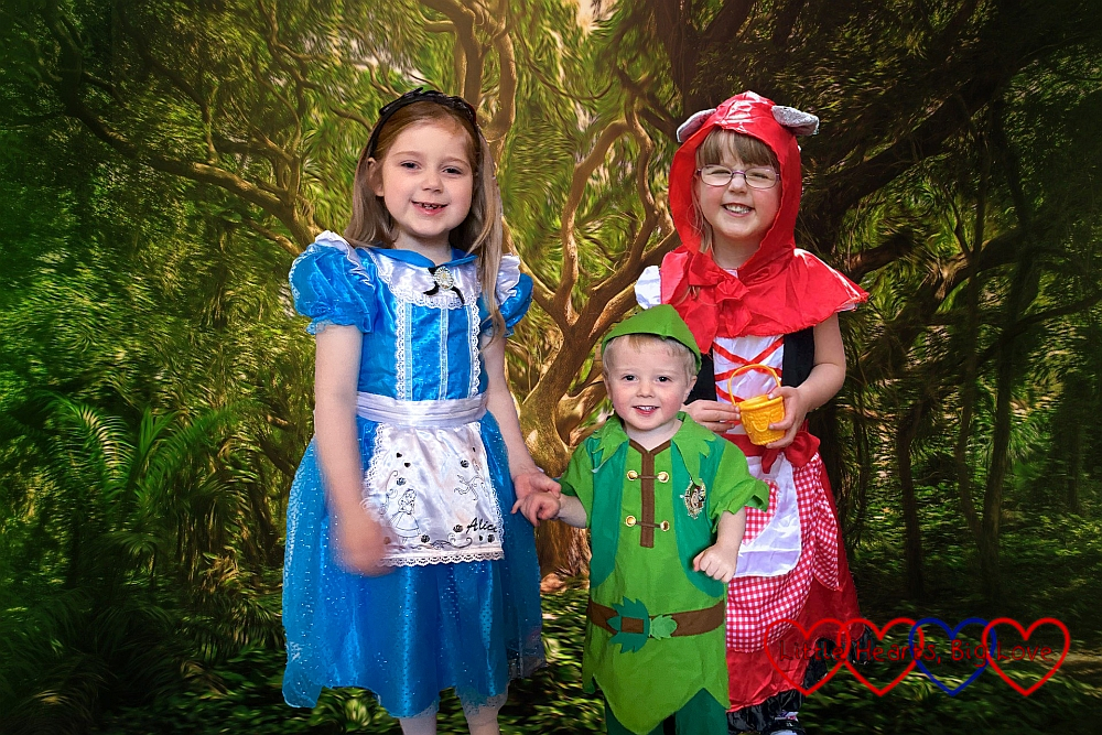 Sophie (dressed as Alice in Wonderland), Thomas (dressed as Peter Pan) and Jessica (dressed as Little Red Riding Hood) with a forest background