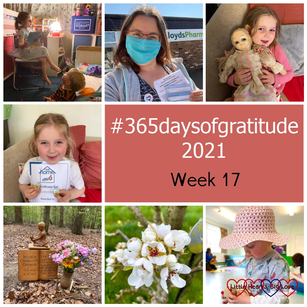 """Sophie reading a bedtime story to Thomas; me wearing a mask with my Covid vaccination card; Sophie holding my favourite dolly; Sophie with her GB@Home certificate and two new badges for her badge bag; pretty flowers at Jessica's forever bed; white apple blossom; Thomas wearing a hat and looking at knitted cakes at Tiny Talk - """"#365daysofgratitude 2021 - Week 17"""""""