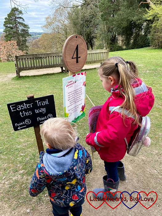 Sophie and Thomas looking at the board under the number 4 marker on the Easter trail