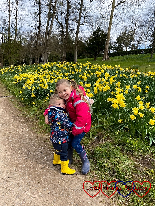 Sophie and Thomas hugging with daffodils in the background