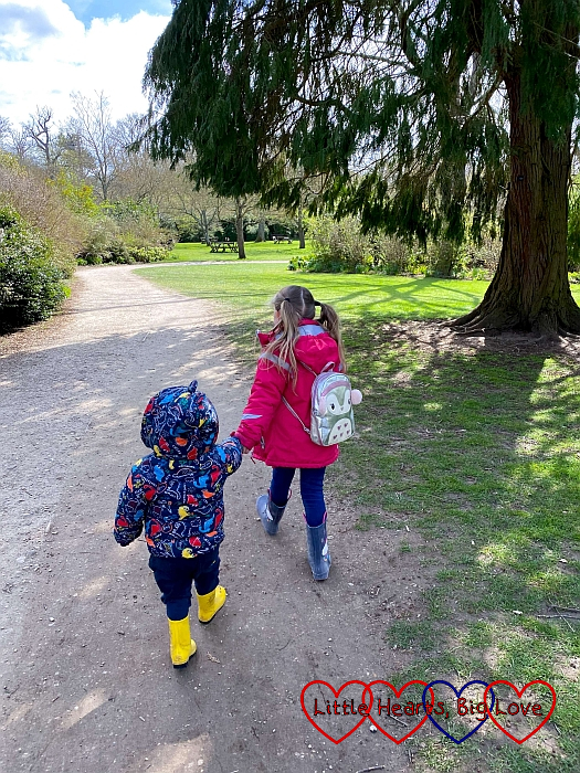Sophie and Thomas walking hand-in-hand down a path at Cliveden