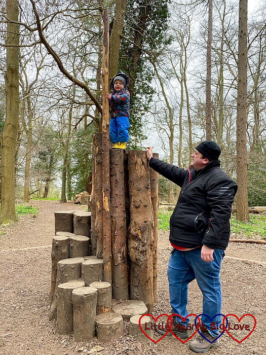 Thomas at the top of a climbing tower made of logs with Daddy standing next to him