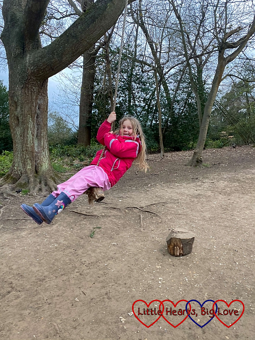 Sophie on a rope swing in the woodland play trail at Cliveden