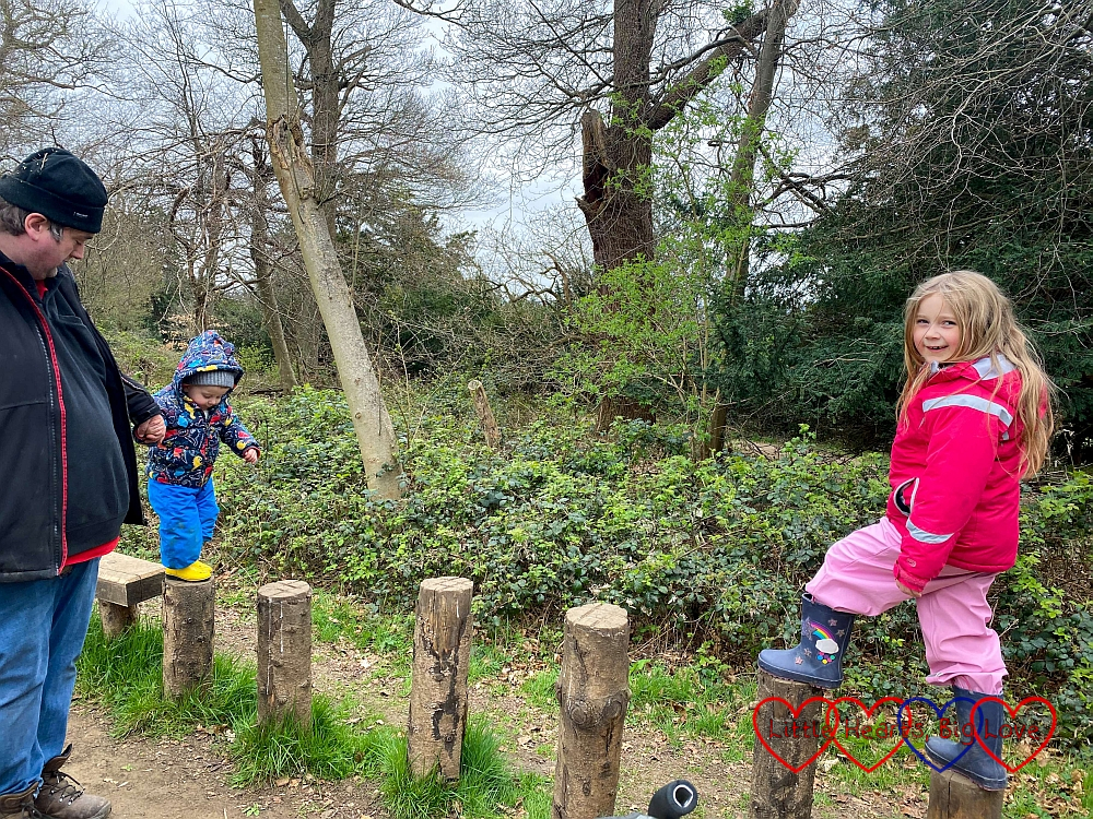 Sophie and Thomas (helped by Daddy) balancing on logs on the play trail at Cliveden
