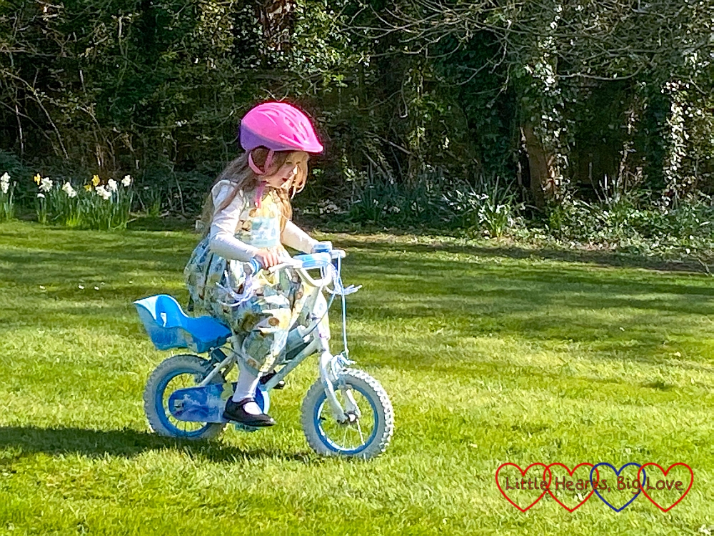Sophie riding her bike without stabilisers on Grandma's lawn