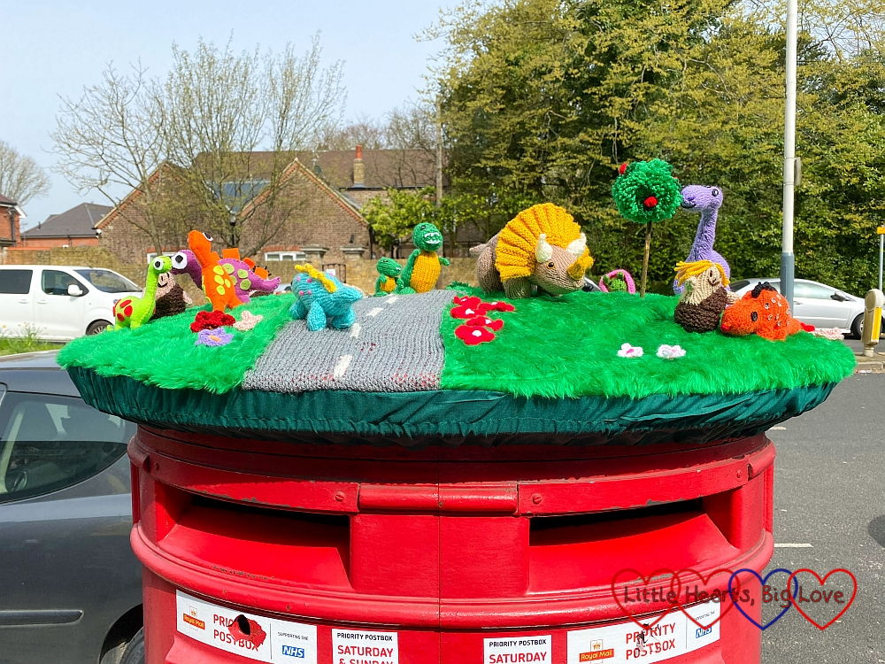 A knitted postbox topper featuring a road with dinosaurs on it