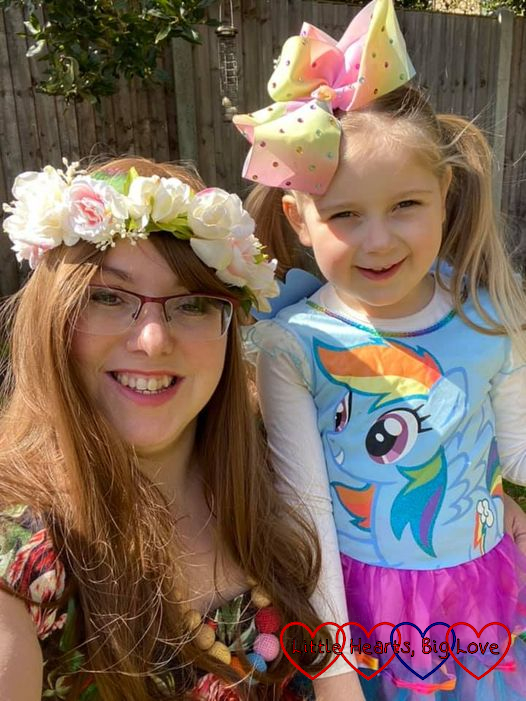Me wearing a wig and a flower crown and Sophie wearing her Rainbow Dash outfit and a big bow in her hair