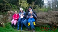 Sophie, me (holding a photo of Jessica) and hubby holding Thomas sitting on a seat carved into a fallen tree