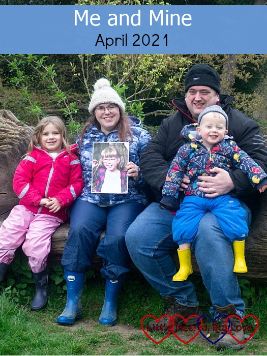 """Sophie, me (holding a photo of Jessica) and hubby holding Thomas sitting on a seat carved into a fallen tree - """"Me and Mine - April 2021"""""""