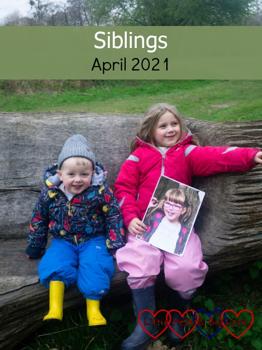 """Sophie and Thomas sitting on a seat carved in a fallen tree with Sophie holding a picture of Jessica - """"Siblings - April 2021"""""""