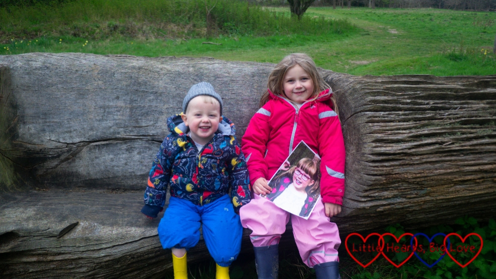 Sophie and Thomas sitting on a seat carved in a fallen tree with Sophie holding a picture of Jessica