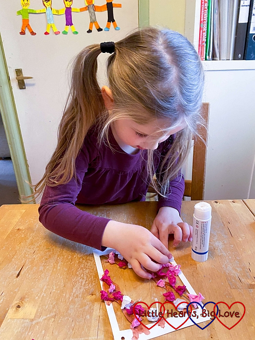 Sophie glueing small pieces of pink tissue paper to a coloured tree outline